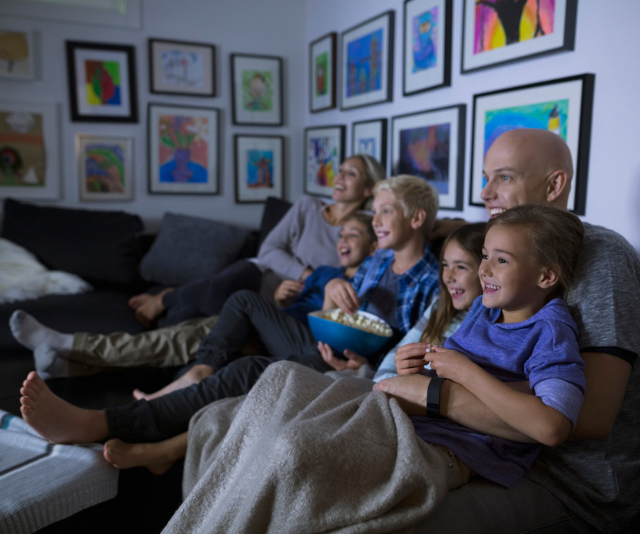 **Make the most of movie night:** Blankets, popcorn, comfy clothes and cuddles ahoy! Load up your favourite movies for a family movie marathon and settle in for some lounge-time bonding. *Image: Getty.*