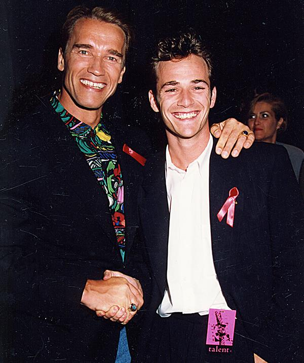His circle of Hollywood friends grew quickly with Perry attending a plethora of glitzy events over the 1990s. Here, he's pictured with none other than Arnold Schwarzenegger at the 1992 MTV Movie Awards. *(Image: Getty)*