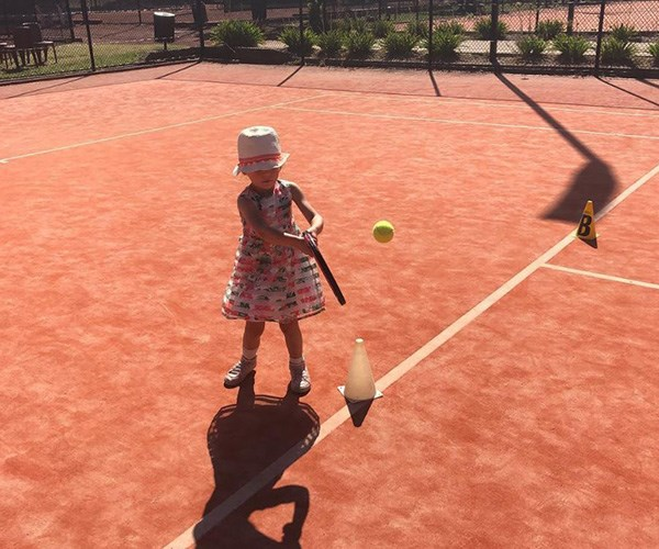 """""""Basically Serena Williams already."""" Proud dad Chris shared this snap of Evie with a tennis racket that's almost as big as her. *(Image: Instagram @walkschris21)*"""