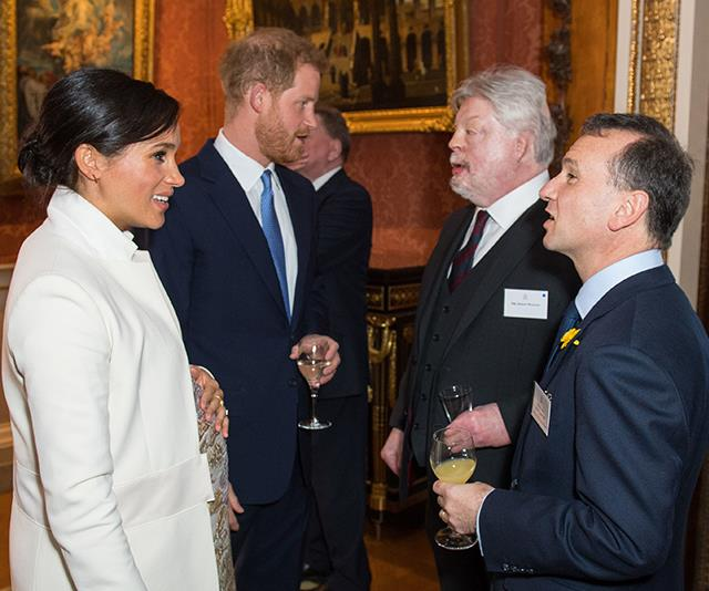 The Duchess cradled her bump as she spoke to guests. *(Image: Getty)*