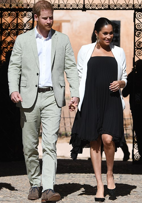 Earlier in the day, Meghan opted for a floaty Loyd/Ford black pleated dress as she and Harry attended a local market in Morocco. *(Image: Getty Images)*