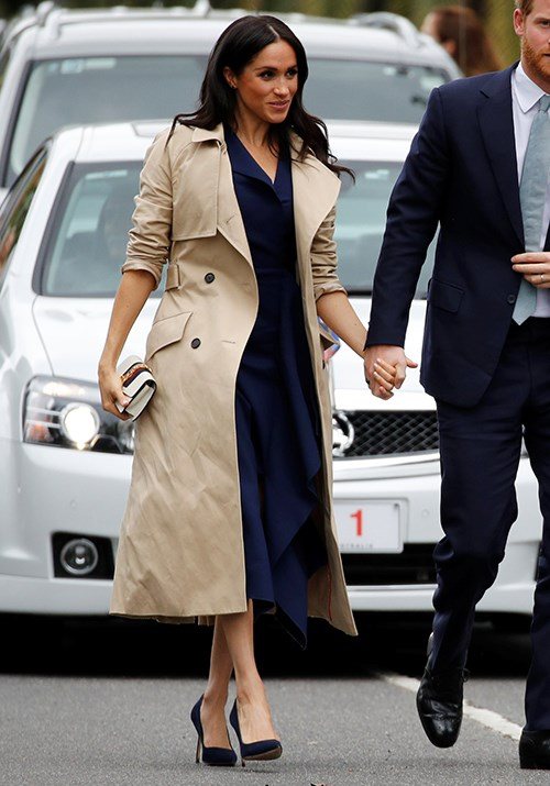 Meghan's Martin Grant trench coat has been worn numerous times by the trendy royal. *(Image: Getty)*