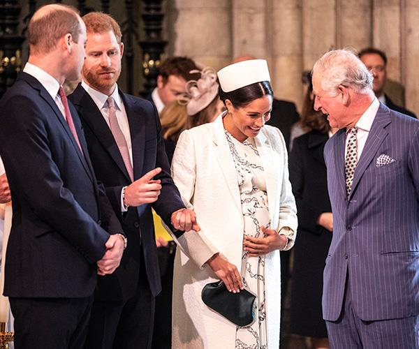 Duchess Meghan holds her bump as she laughs with Prince Charles. *(Image: Getty Images)*