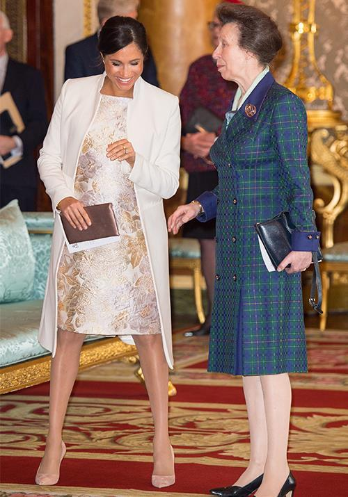 Royal confidantes Duchess Meghan and Princess Anne share a laugh during celebrations for Prince Charles' 50-year investiture. *(Image: Getty)*
