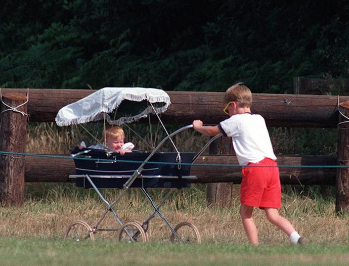 Too cute! Proving he's the ultimate older cousin, Prince William pushes Princess Beatrice around in a pram in 1989. *(Image: Getty)*