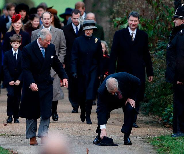 Whoops! Prince Andrew's hat topples off and older brother Prince Charles finds it most amusing. *(Image: Getty)*