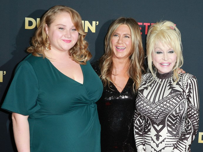 *Dumplin* stars Danielle Macdonald and Jennifer Aniston with Dolly Parton at the film's premiere. *(Image: Getty)*