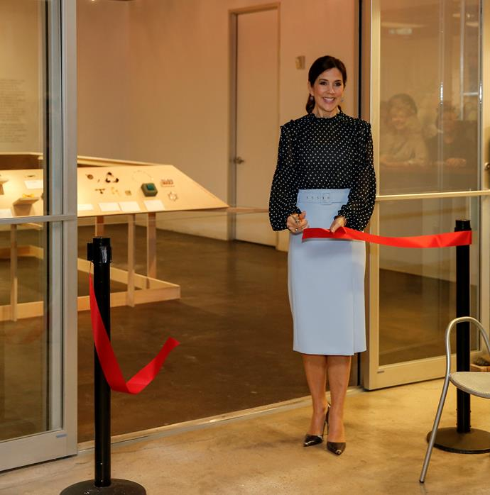 The following day, Mary wore a chic powder blue skirt and chiffon polka dot shirt as she helped open the Danish jewellery exhibition in Texas - a very fitting event for the stylish Princess. *(Image: Getty)*