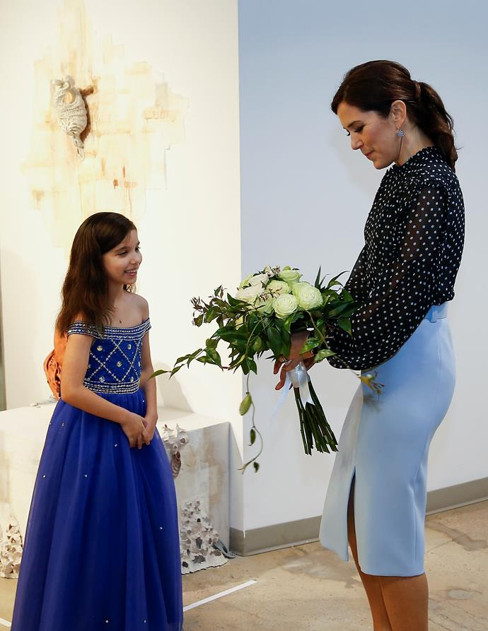 Too sweet! The Princess received a bunch of flowers from a very excited young guest - this is starting to feel like a real life fairytale! *(Image: Getty)*