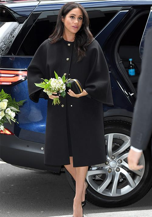 Meghan looked stunning in a black button-down coat and heels. *(Image: Getty)*