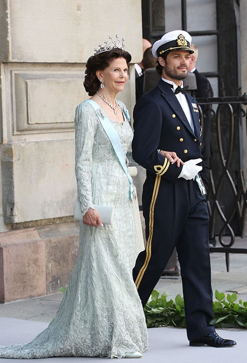 A queen and her son: Queen Silvia of Sweden and Prince Carl Philip at the wedding of Princess Madeleine of Sweden in 2013.