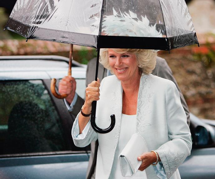 Camilla making sure those feathers on her hat stay dry. *(Image: Getty)*