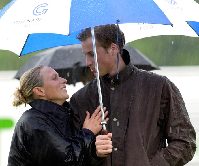 A dashing young Prince William keeping his cousin Zara Phillips dry during a particularly wet polo match in 2004. *(Image: Getty)*