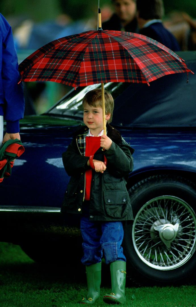 Now this is just too cute! An adorable young Prince William being very grown up holding his own umbrella. *(Image: Getty)*