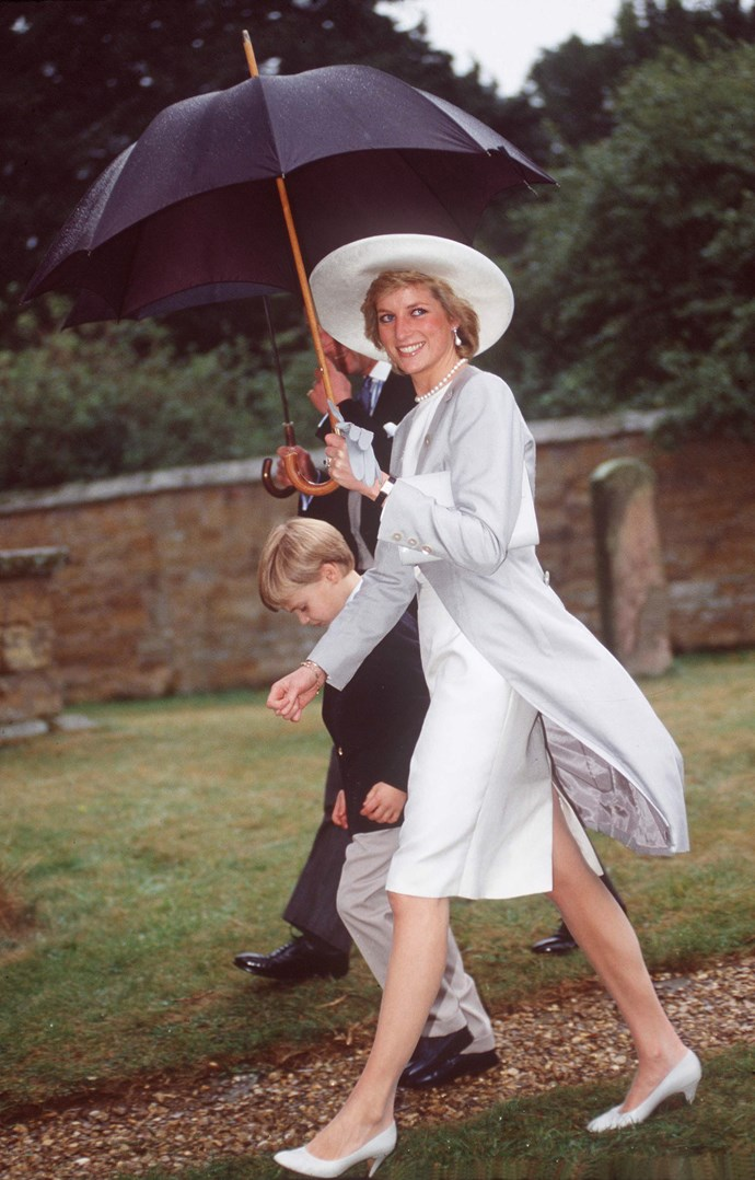 The gorgeous Princess Diana didn't let the rain bother her! Here she is striding with confidence on a drab British day. *(Image: Getty)*