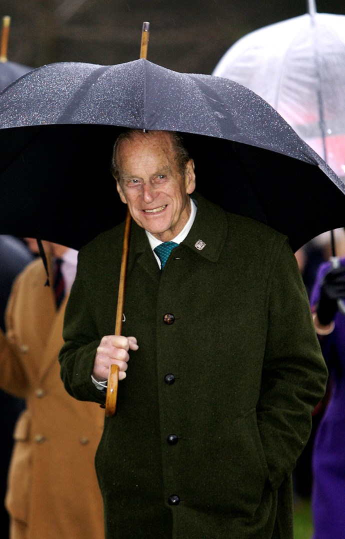 He might be pushing 100, but Prince Philip can still do pretty much everything on his own, including keeping himself out of the rain. *(Image: Getty)*