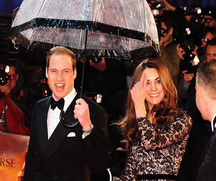 What a gentleman! Prince William kept his wife Catherine dry while walking the very wet red carpet at the 2012 premiere of the film *War Horse*. *(Image: Getty)*