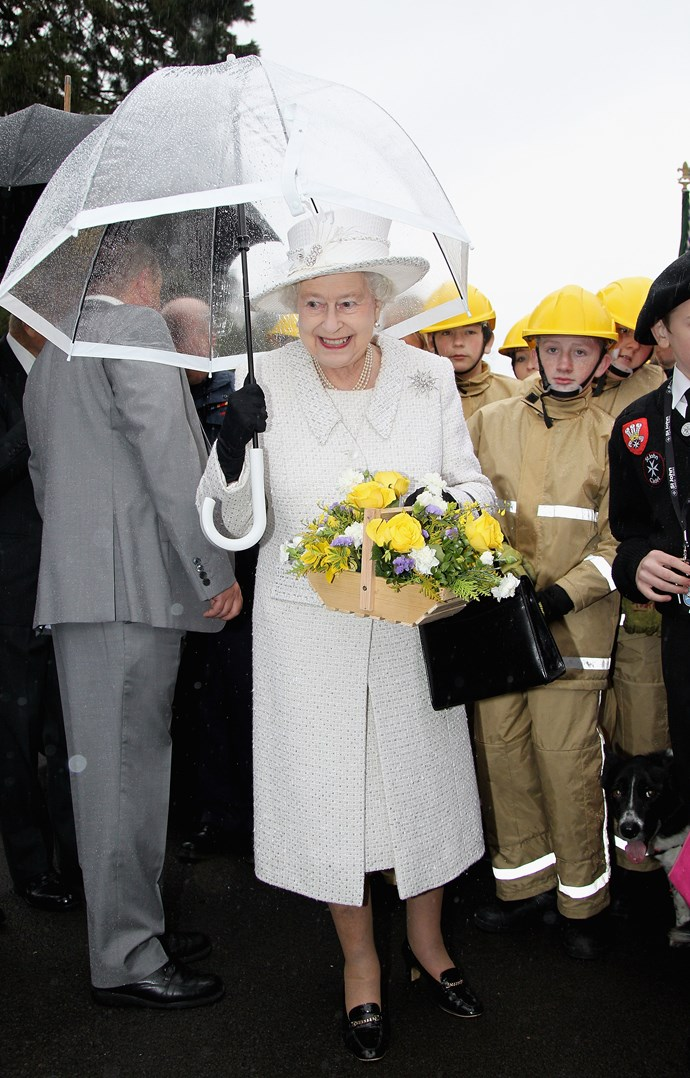 The Queen keeping it classic in all-white, bringing some much-needed freshness to the dreary weather. *(Image: Getty)*
