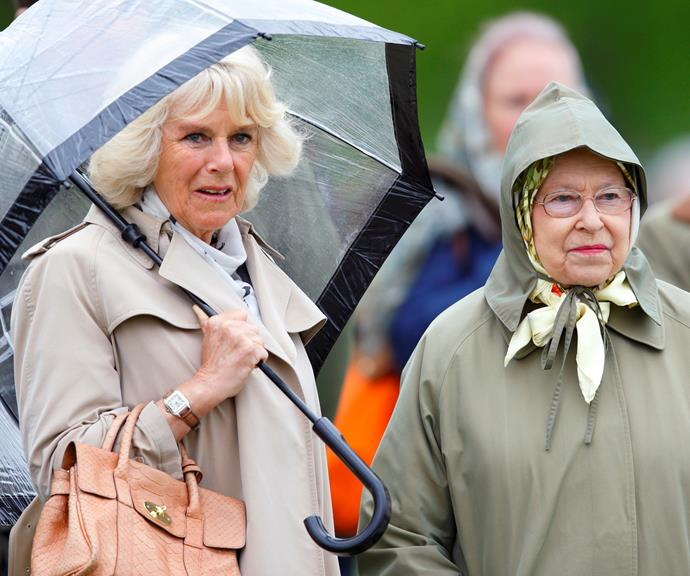 Camilla, the Duchess of York, kept herself dry under an umbrella while the Queen touged it out in a very practical raincoat. *(Image: Getty)*