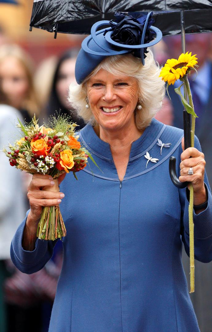 Get you a girl who can do both! Camilla has her hands full with her umbrella, a pretty bouquet of flowers and a single sunflower. *(Image: Getty)*