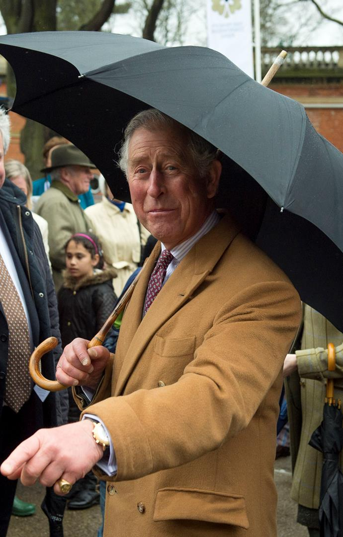 Prince Charles keeping himself dry while out and about chatting to punters. *(Image: Getty)*