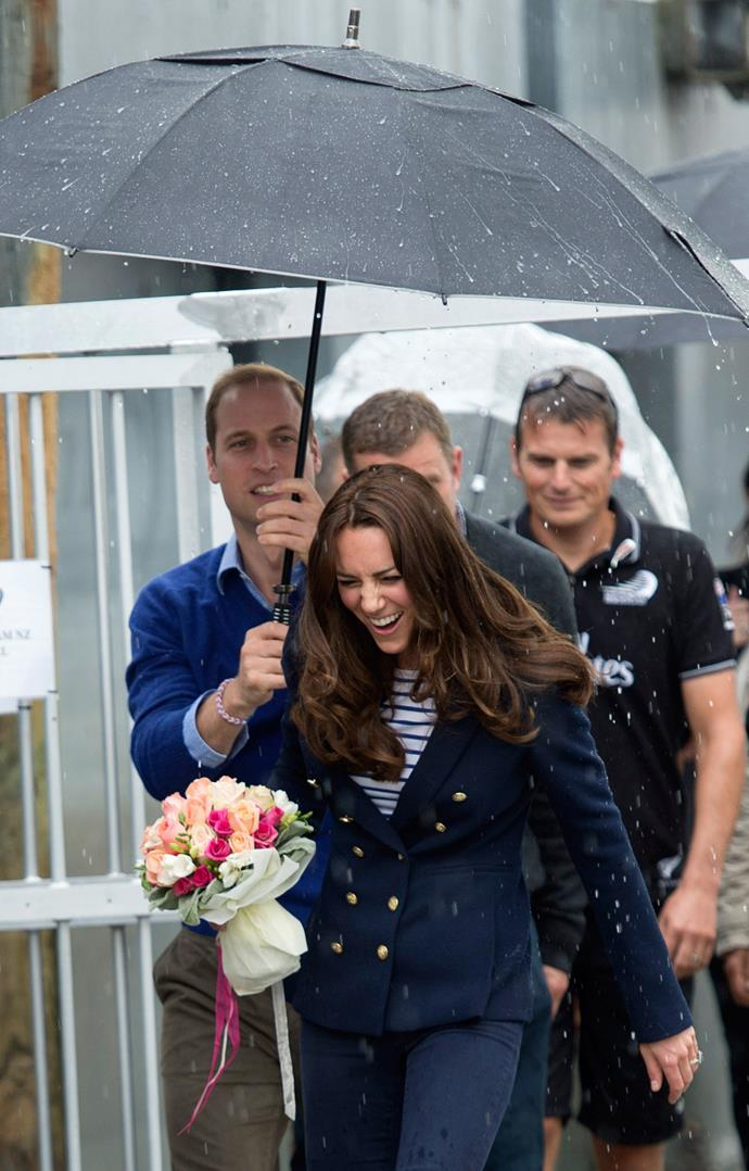 Can you see Prince William in the background? He's doing his best to keep Kate dry in the pouring rain, bless him! *(Image: Getty)*
