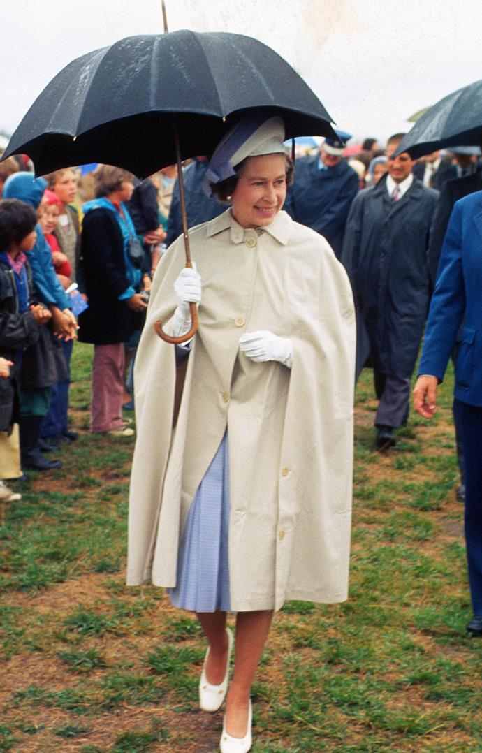 And again, a younger Queen braving the elements in a gorgeous outfit. *(Image: Getty)*
