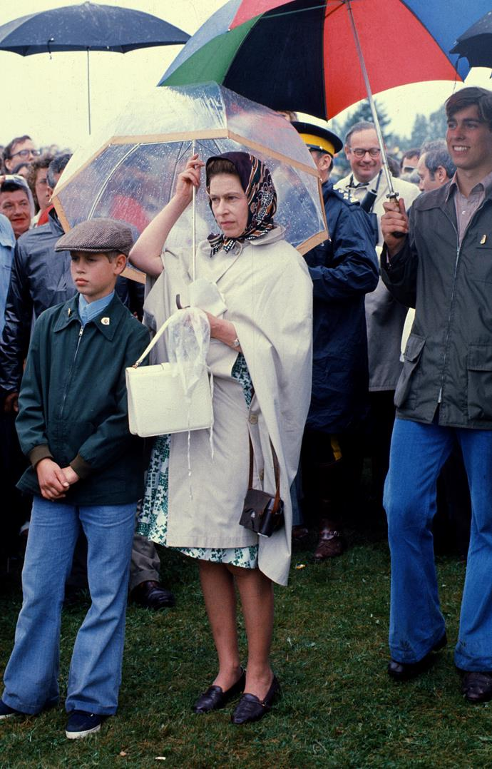 Queen Elizabeth with a very young Prince Charles, on a classic wet English day. *(Image: Getty)*