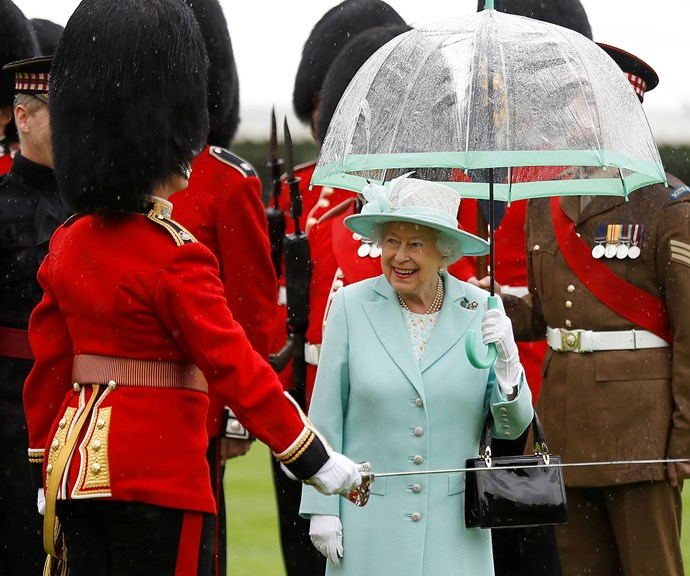The Queen always holds her own umbrella. In fact, she's got a whole wardrobe full of them in different colours, to match all of her different outfits, just like this pretty mint one. *(Image: Getty)*