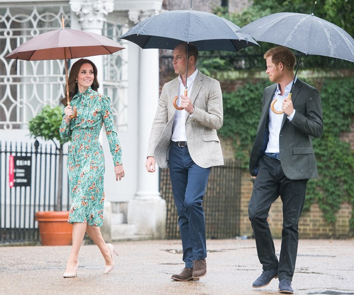 What a trio! Duchess Catherine, Prince William and Prince Harry pose for a photocall while casually strolling through the rain. *(Image: Getty)*