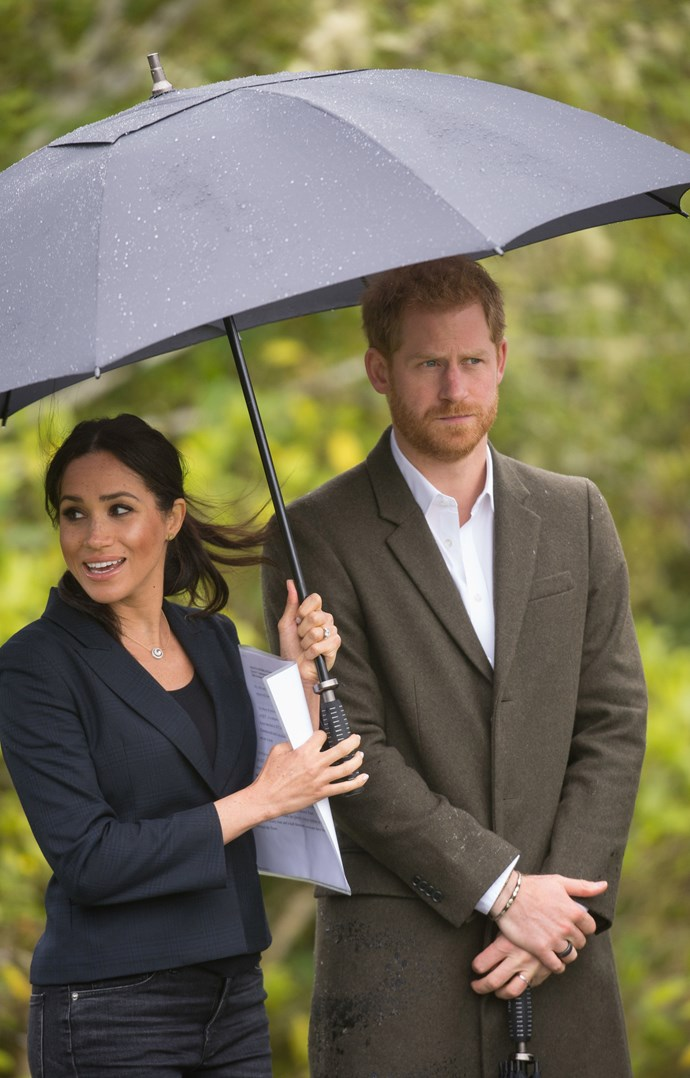 """I've got this babe!"" - Meghan proving once again that she doesn't need a man to hold her umbrella for her. *(Image: Getty)*"