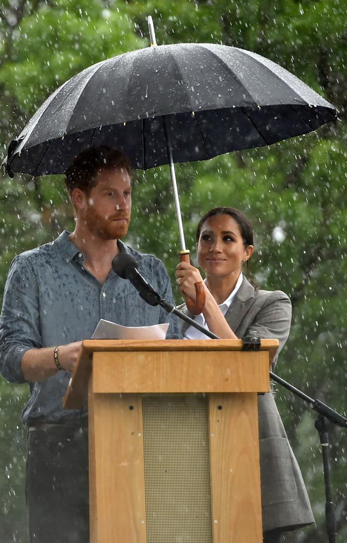 Who could forget this moment during Harry and Meghan's royal tour of Australia, when the Duchess held an umbrella over her husband while he gave a speech in Dubbo? Just gorgeous. *(Image: Getty)*