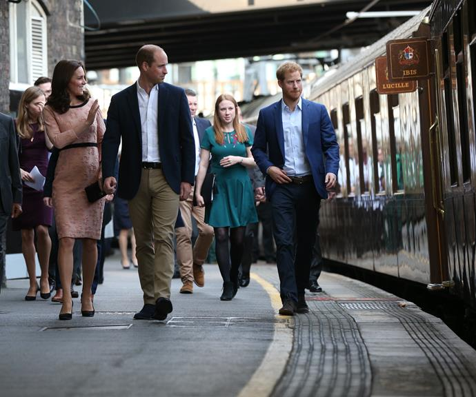 Duchess Catherine, Prince William and Prince Harry walk through a London train station. *(Image: Getty)*