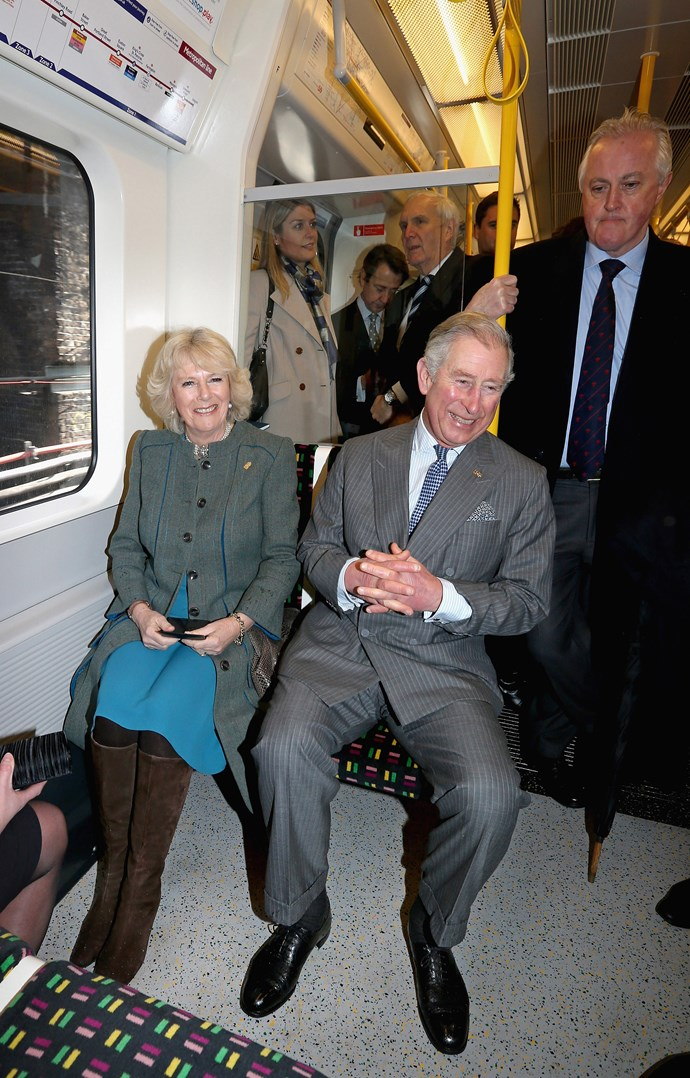Camilla and Prince Charles sharing a laugh on the tube. *(Image: Getty)*