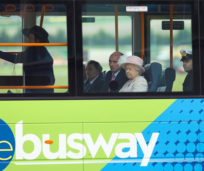The Queen rides with her entourage on a very empty British bus. *(Image: Getty)*
