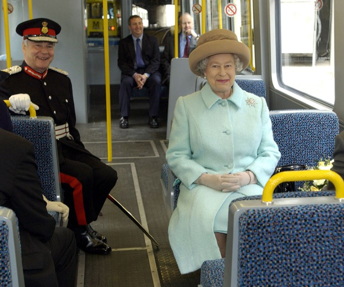 This looks a little different to our packed morning bus! The Queen sitting patiently on a London bus.*(Image: Getty)*