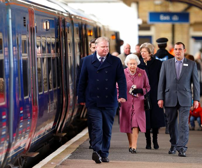 The Queen flanked by her bodyguards as she gets ready to board a train. *(Image: Getty)*
