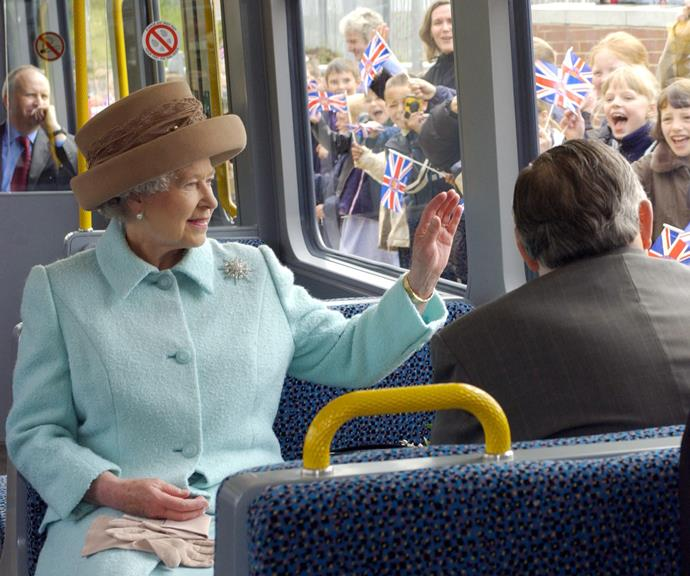 Looking gorgeous in pale blue as she waves to excited schoolchildren waiting outside. *(Image: Getty)*