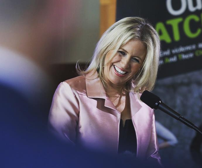 Chloe is an ambassador for domestic violence prevention organisation Our Watch and is a passionate advocate for women's rights. She's pictured here smiling adoringly at her husband while delivering a keynote speech. *(Image: Getty)*