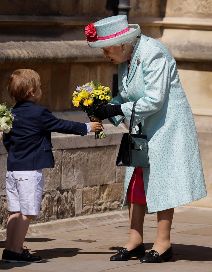 The Queen receives a bunch of flowers from a very cute onlooker after the service. *(Source: Getty Images)*