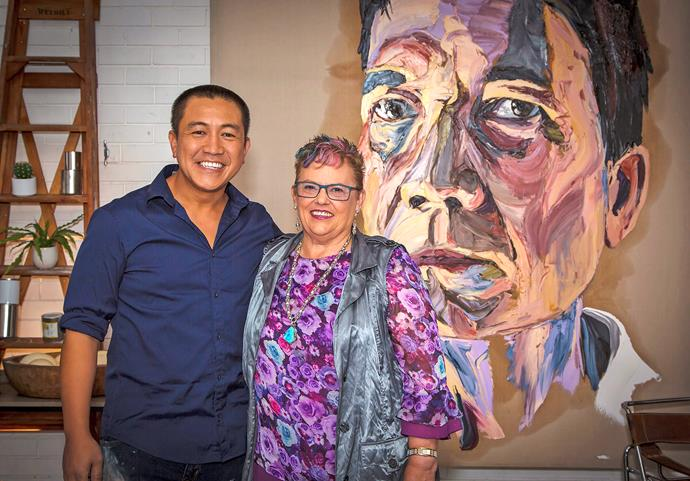 Anh Do and Lindy pose in front of a painting, not of Lindy, in Anh's painting studio. (Image: ABC).