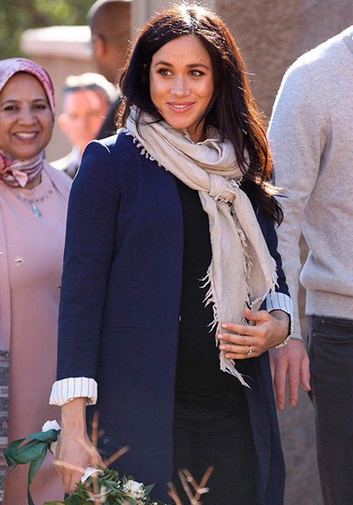 Wearing a black long-sleeve top and scarf, Meghan dressed up her casual look here with a smart blue blazer - genius! *(Image: Getty)*
