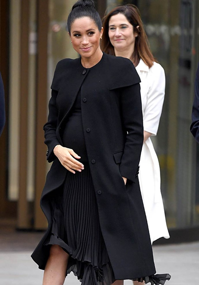 Meghan's black Givenchy coat made the royal look powerful and feminine. *(Image: Getty)*