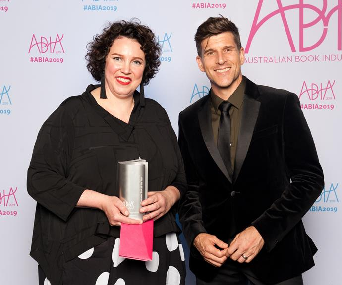 Osher Gunsberg celebrates a win for Hetty McKinnon's book *Family: New vegetable classics to comfort and nourish*, with the book's publisher from Pan Macmillan Australia. *(Image: Supplied)*