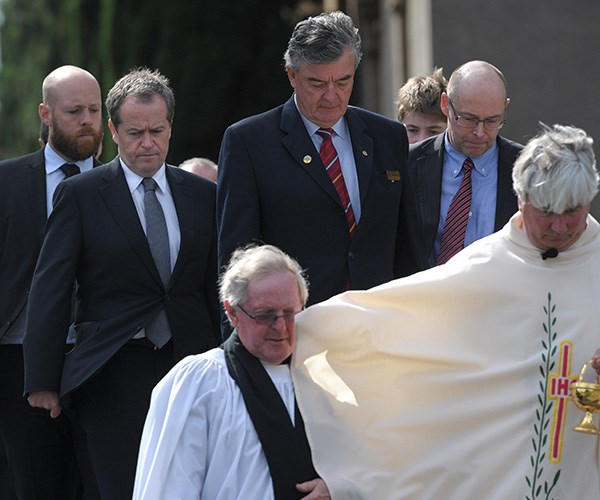 Bill Shorten assists in carrying his mother's casket at her funeral in 2014. *(Image: AAP)*