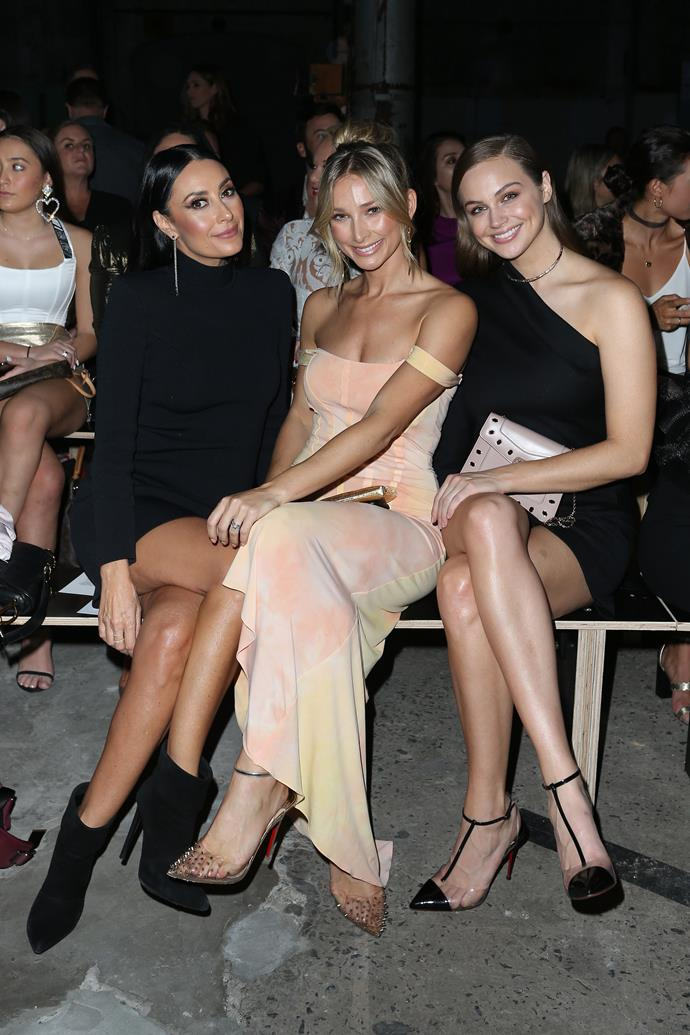 Former *The Bachelor* contestant Anna Heinrich, who is married to Tim Robards, was also front row at Carla Zampatti wearing a pretty sorbet-coloured dress. She's pictured here with WAG Terry Biviano (left) and E! News host Ksenija Lukich. *(Image: Getty)*