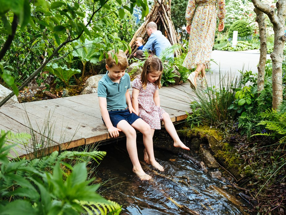 Prince George and Princess Charlotte dangle their feet in the stream. *(Image: Matt Porteous /@ KensingtonRoyal)*