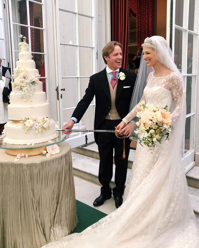 The gorgeous couple cut their cake at their wedding reception.