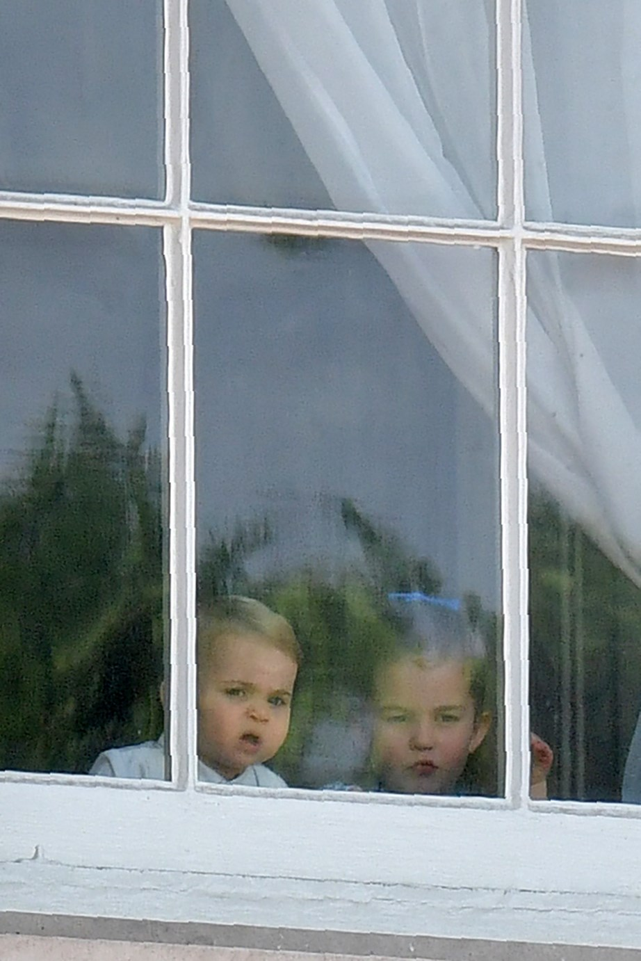 Prince Louis and Princess Charlotte sneak a peek outside the Palace windows. *(Image: Getty)*
