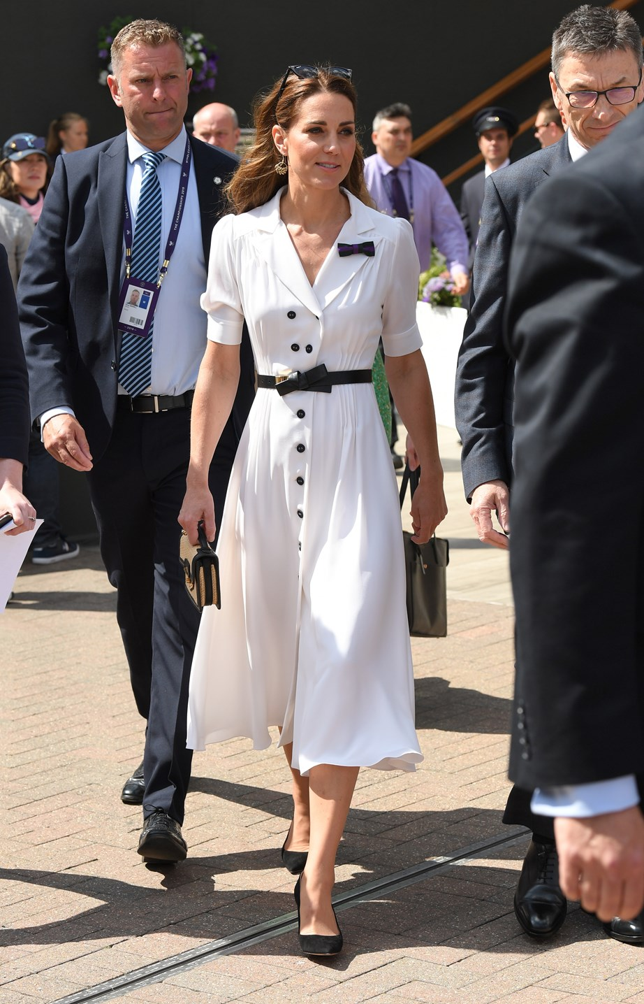 Kate looked gorgeous in a chic white shirt dress accessories with a black belt, heels and sunglasses. *(Image: Getty)*